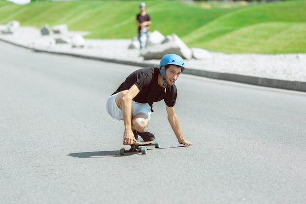 Skateboarder doet een truc in de straat van de stad op zonnige dag.