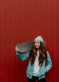 Skateboardermeisje en haar schaats in de stad