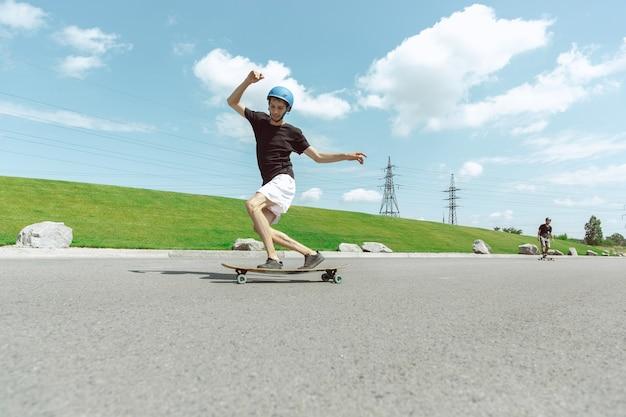 Skateboarders doen op zonnige dagen een truc in de straat van de stad. jonge mannen in uitrusting rijden en longboarden op het asfalt in actie. concept van vrijetijdsbesteding, sport, extreem, hobby en beweging.