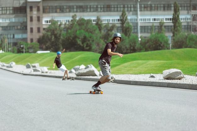 Skateboarders doen op zonnige dagen een truc in de straat van de stad