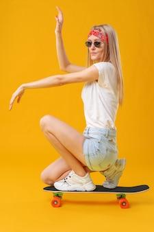 Skateborder meisje in korte broek en t-shirt zitten aan boord op gele achtergrond