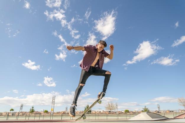 Skater met skateboard doet truc in skatepark