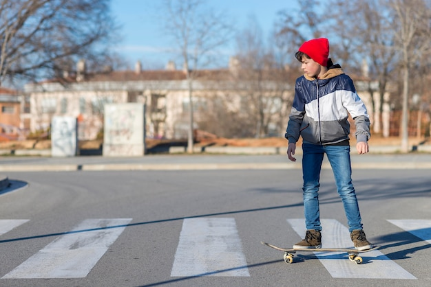 Skater-tiener met een hoed aan boord op straat