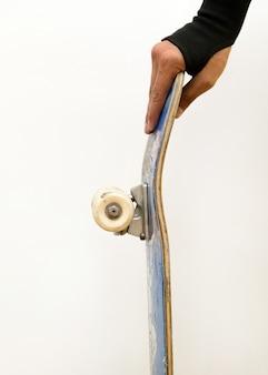 Skaterhand met een beschermende polsbescherming met skateboarddek.
