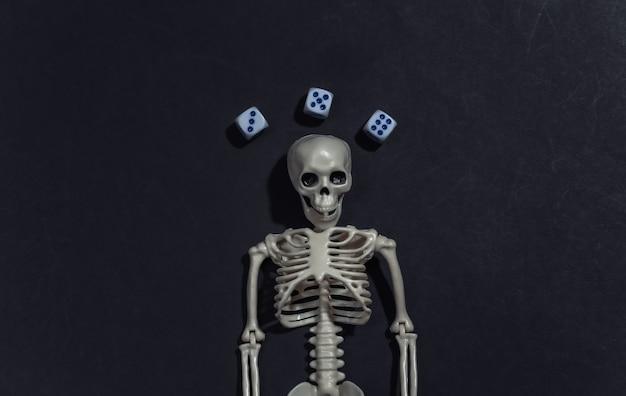 Skelet en dobbelstenen op zwarte achtergrond. gokverslaving.