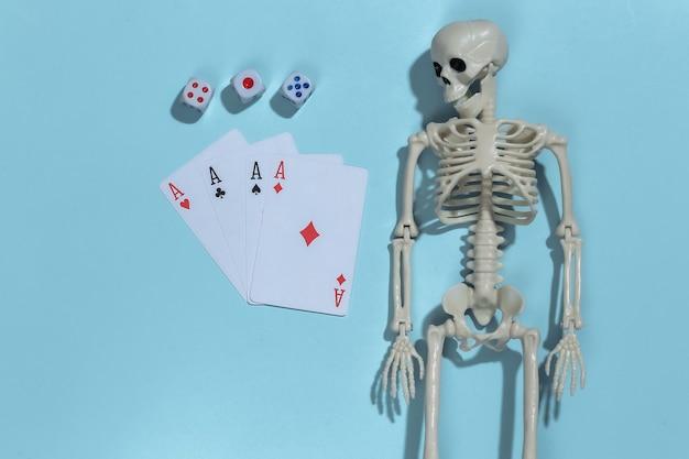 Skelet en vier azen, dobbelstenen op blauwe achtergrond. gokverslaving.