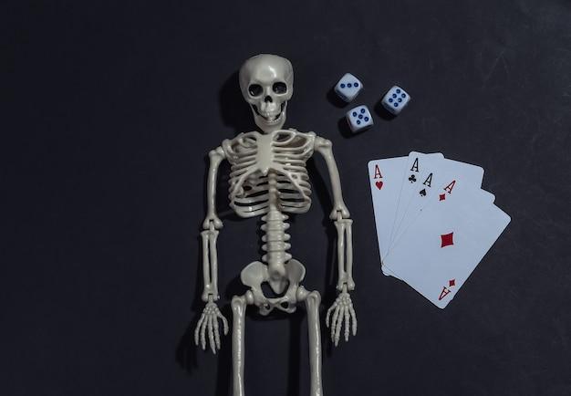 Skelet en vier azen, dobbelstenen op zwarte achtergrond. gokverslaving.