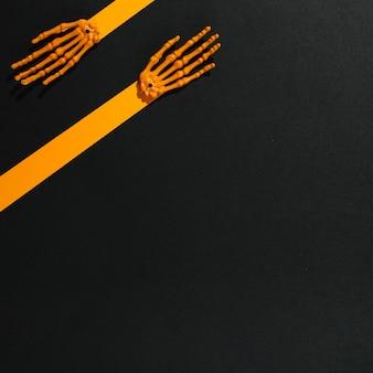 Skelet handen gemaakt van stukjes oranje papier en botten
