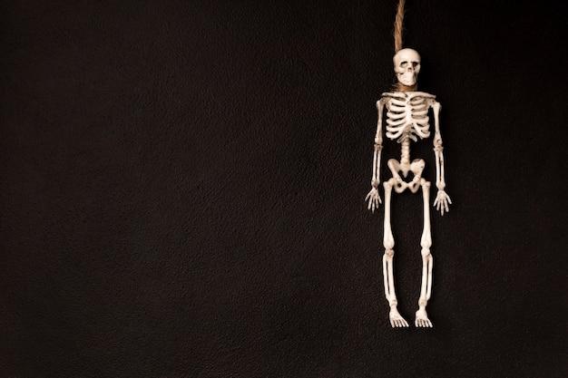 Skelet in de vorm van een opgehangen man plat lag op een donkere achtergrond met kopie ruimte. uitnodiging voor halloween-vakantie.