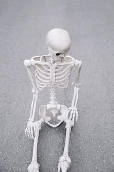 Skelet zittend op de weg en naar beneden te kijken