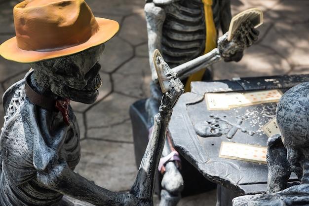Skeletbot spook met cowboyhoed speel rummy-kaarten met vrienden op tafel.
