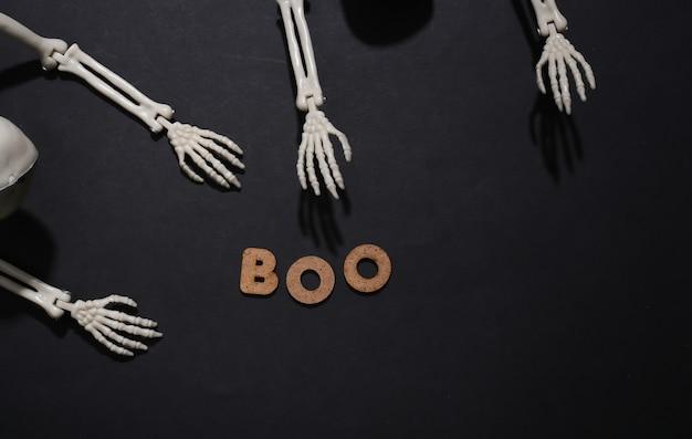 Skelethanden en het woord boe op een zwarte achtergrond. halloween-thema