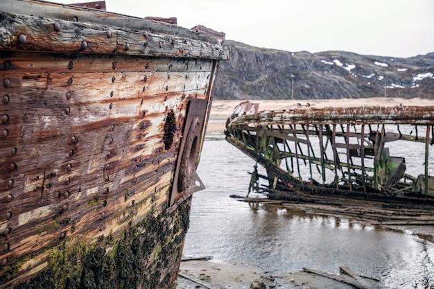 Skeletten van vernielde schepen aan de kust