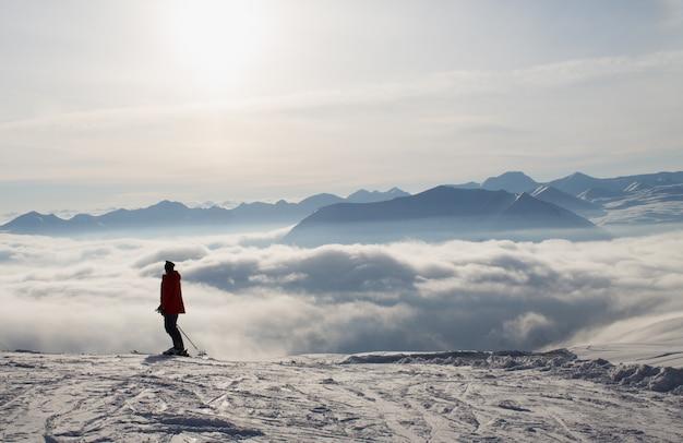 Skiër bovenop de sneeuwbergen, boven de wolken, zonsondergangzon. de bergen van de kaukasus in de winter, georgië