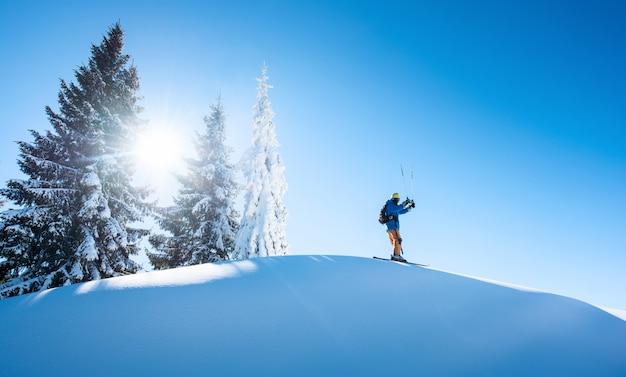 Skiër die bovenop de berg rust