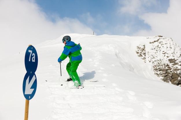 Skiër die de heuvel op skiër loopt