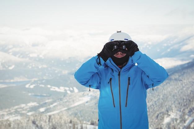 Skiër die door verrekijker kijkt