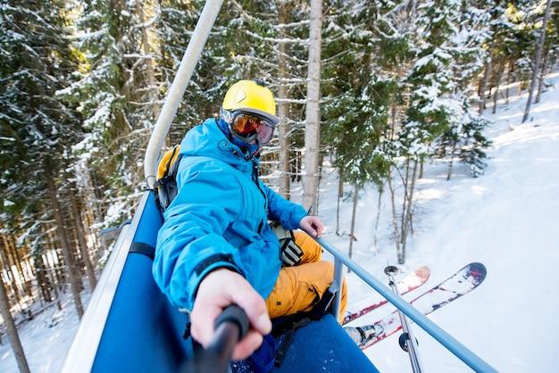 Skiër die een selfie in de skilift neemt