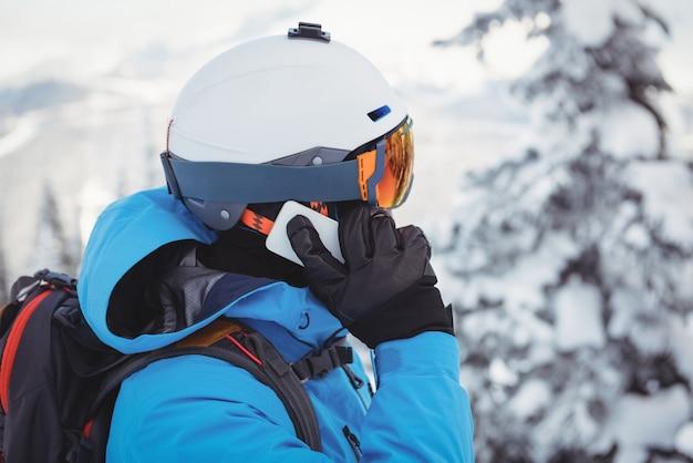 Skiër die op mobiele telefoon spreekt
