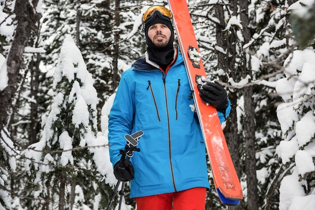 Skiër die op sneeuw behandelde bergen loopt