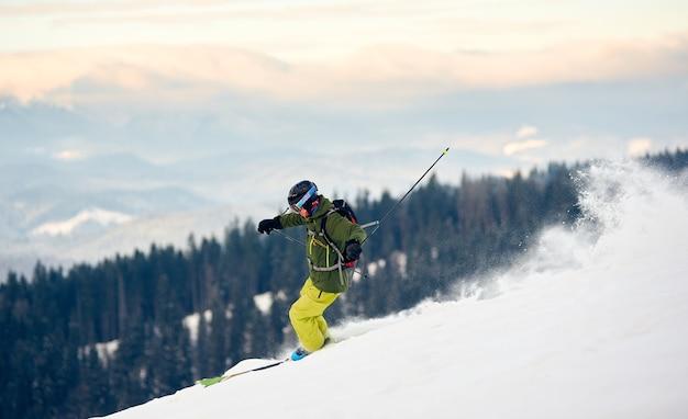 Skiër die van met sneeuw bedekte hoge bergtop afdaalt