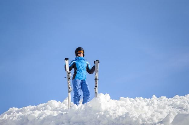 Skiër die zich bovenop de berg tegen blauwe hemel op een zonnige dag bevindt