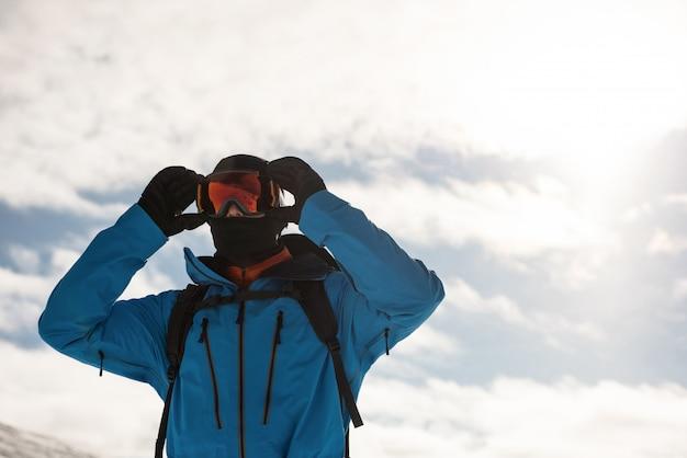 Skiër die zijn zonnebril aanpast