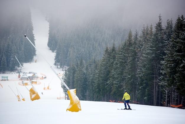 Skiër doet freeriding afdaling in sneeuwval op berghelling met stoeltjeslift onder dicht naaldbos. achteraanzicht