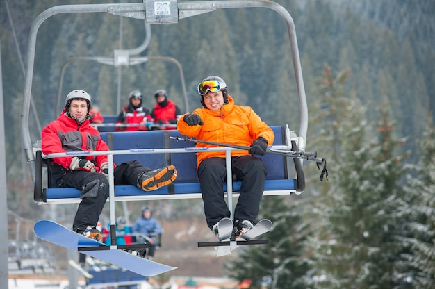 Skiër en snowboarder die omhoog op skilift berijdt