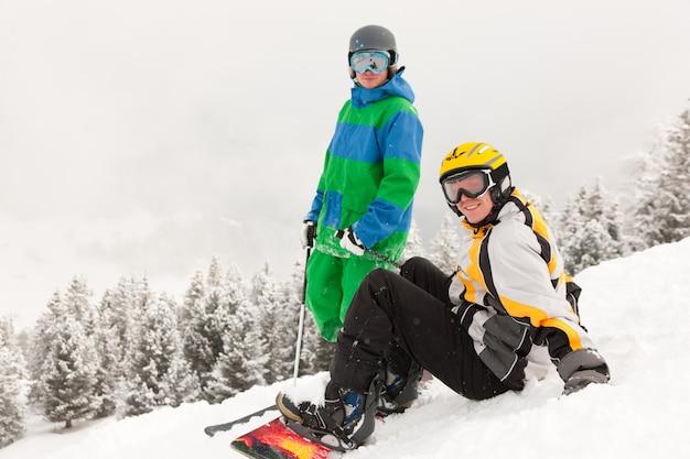 Skiër en snowboarder op berg