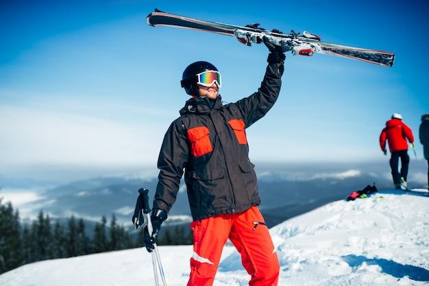 Skiër in helm en bril houdt ski's en stokken in handen, blauwe lucht en besneeuwde bergen. actieve wintersport, extreme levensstijl. bergafwaards skiën