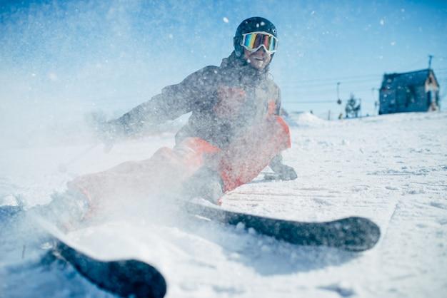 Skiër in helm en bril ligt op besneeuwde ondergrond van snelheidshelling, vooraanzicht. actieve wintersport, extreme levensstijl. bergafwaards skiën