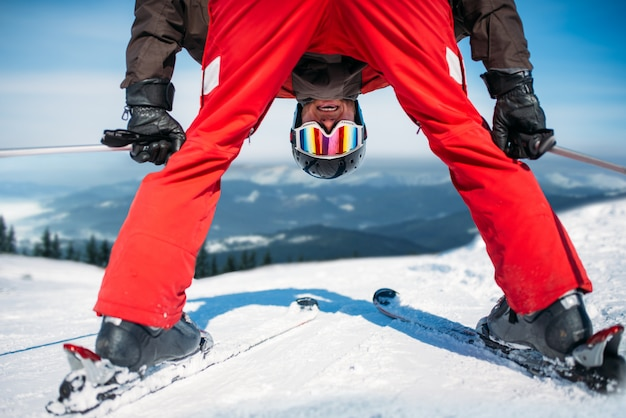 Skiër in helm en bril, onderaanzicht. actieve wintersport, extreme levensstijl. alpineskiën of bergskiën