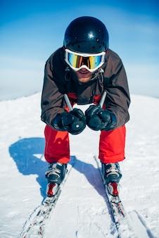 Skiër in helm en bril racen vanaf de berg, vooraanzicht. actieve wintersport, extreme levensstijl. bergafwaards skiën