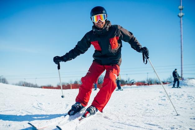 Skiër in helm en bril rijden vanaf snelheidshelling, vooraanzicht. actieve wintersport, extreme levensstijl. bergafwaards skiën
