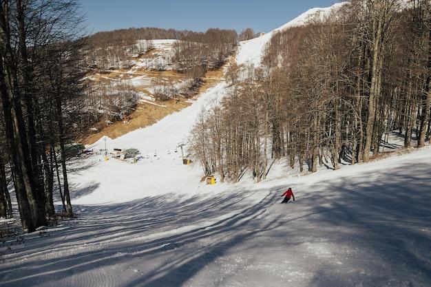 Skiër in rode jas skiën op verse sneeuw