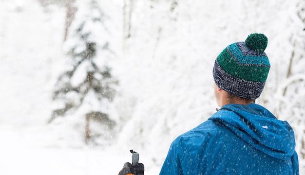 Skiër in windjack en muts met pompon met skistokken in zijn handen met zijn rug op een besneeuwd bos. langlaufen in winterbos, buitensporten, gezonde levensstijl.