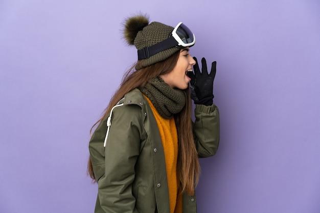 Skiër kaukasisch meisje met snowboard bril geïsoleerd op paarse achtergrond schreeuwen met mond wijd open naar de zijkant