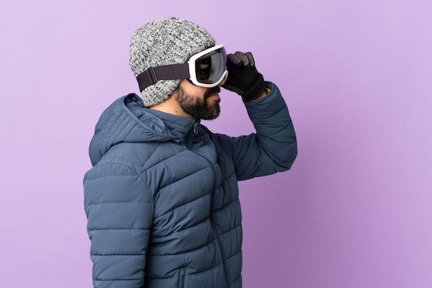 Skiër man met snowboard bril op geïsoleerde paars