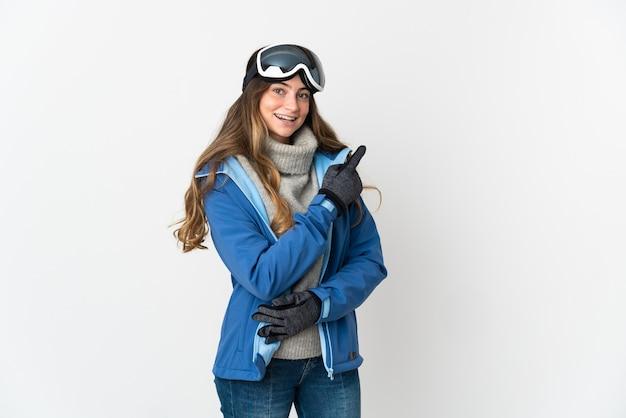 Skiër meisje met snowboard bril op wit wijzende vinger naar de zijkant