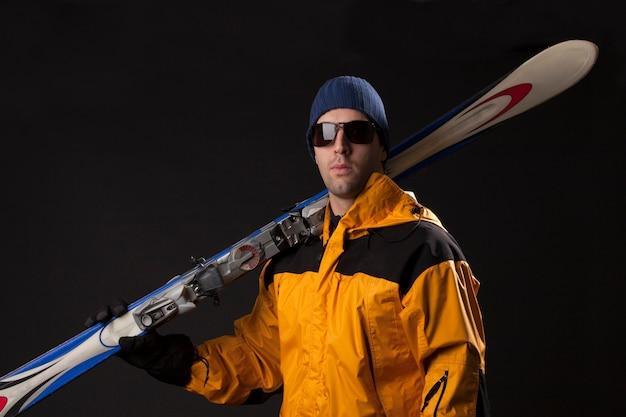 Skiër met een paar ski's op een zwarte muur