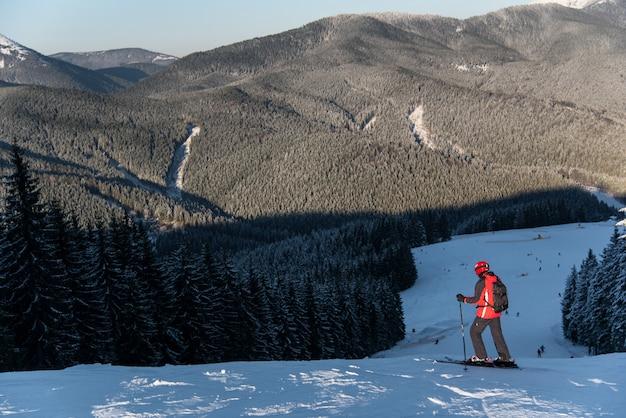 Skiër op de top van afdaling genieten van bergen en bossen