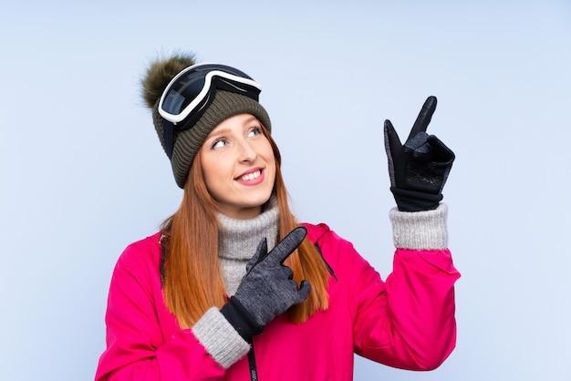 Skiër roodharige vrouw met snowboard bril wijst met de wijsvinger een geweldig idee