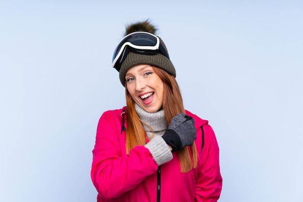 Skiër roodharigevrouw die met snowboarding glazen over geïsoleerde blauwe muur een overwinning vieren