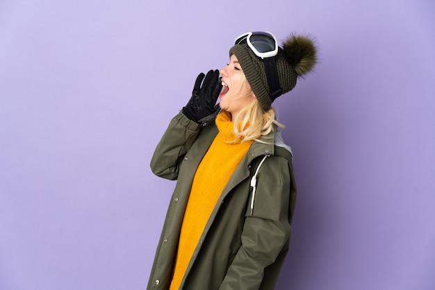 Skiër russisch meisje met snowboard bril geïsoleerd op paarse achtergrond schreeuwen met mond wijd open aan de zijkant