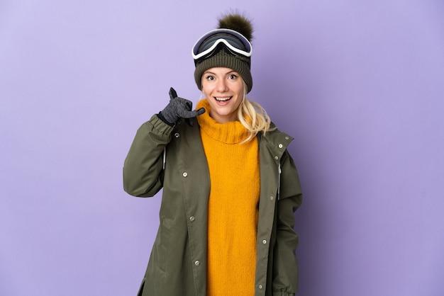 Skiër russisch meisje met snowboard bril geïsoleerd op paarse achtergrond telefoon gebaar maken. bel me terug teken