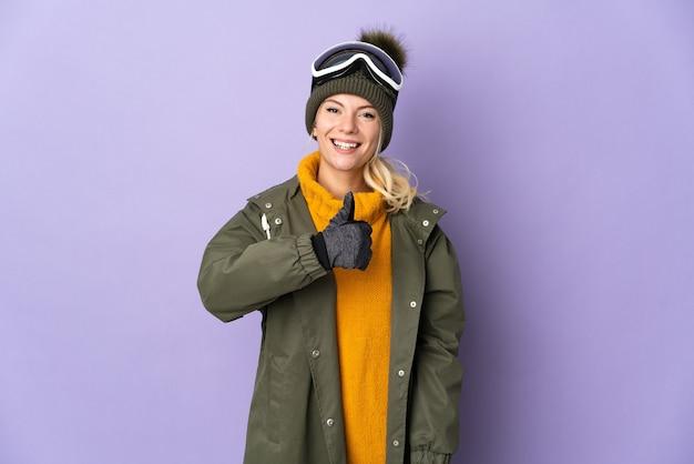 Skiër russisch meisje met snowboardbril geïsoleerd op paarse achtergrond met een duim omhoog gebaar
