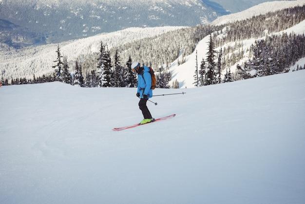Skiër skiën op besneeuwde bergen