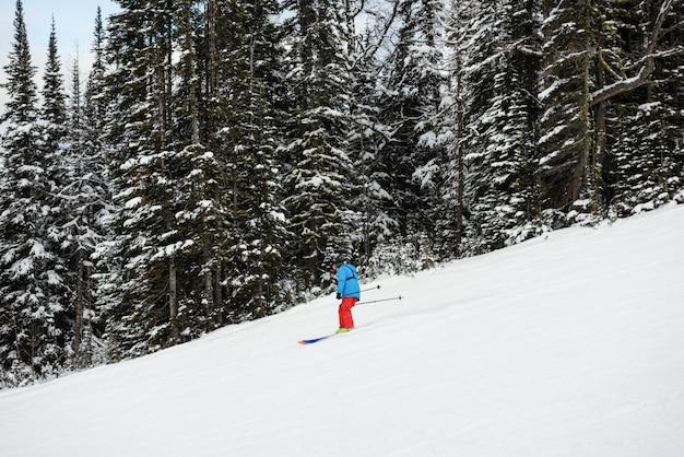 Skiër skiën op besneeuwde berghelling