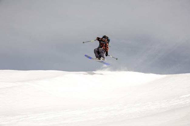 Skiër springt hoog in de lucht terwijl hij bij bewolkt weer van de berg glijdt